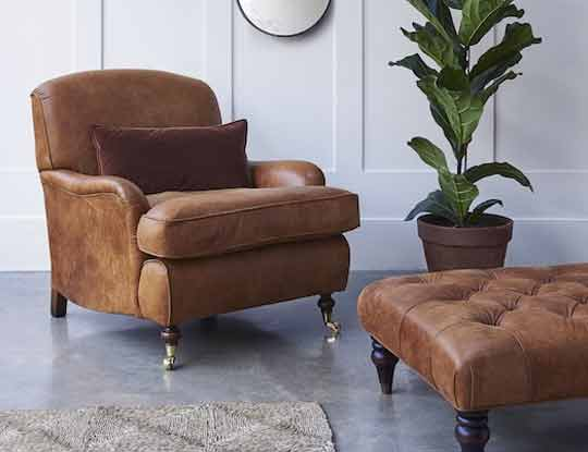rust leather armchair and footstool in room set